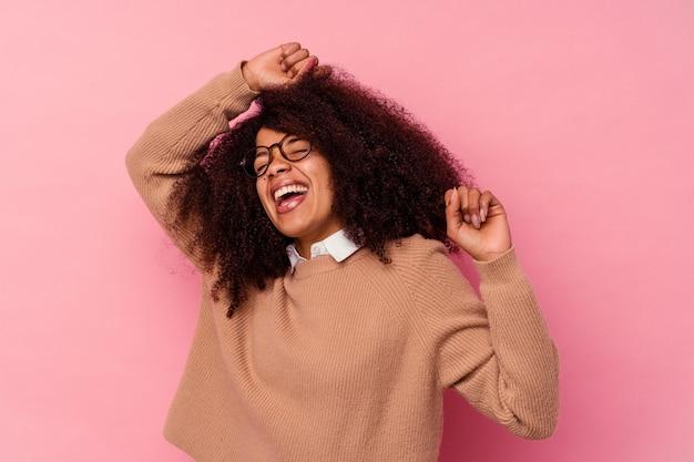 Junge afroamerikanerin, die auf rosa isoliert ist und einen besonderen tag feiert, springt und hebt die arme mit energie.