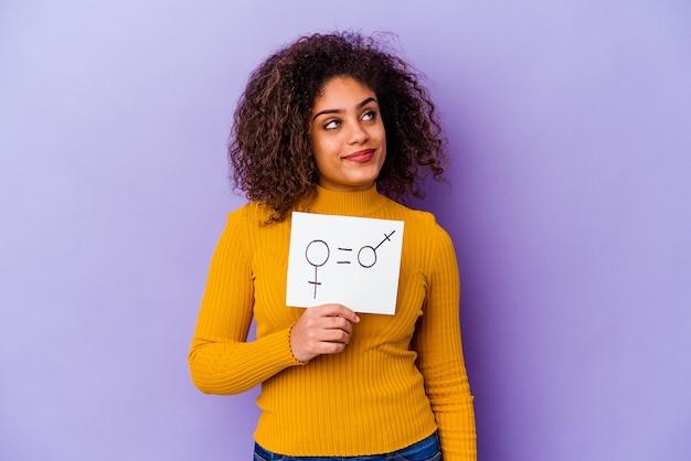 Junge afroamerikanerin, die ein auf violettem hintergrund isoliertes plakat zur gleichstellung der geschlechter hält und davon träumt, ziele und zwecke zu erreichen