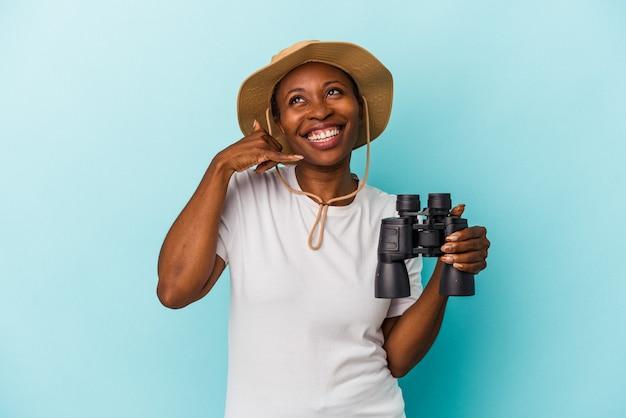 Junge afroamerikanerin, die ein fernglas auf blauem hintergrund hält, das eine handy-anrufgeste mit den fingern zeigt.
