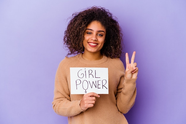 Junge afroamerikanerin, die ein girl-power-plakat hält, das auf lila hintergrund isoliert ist und die nummer zwei mit den fingern zeigt.