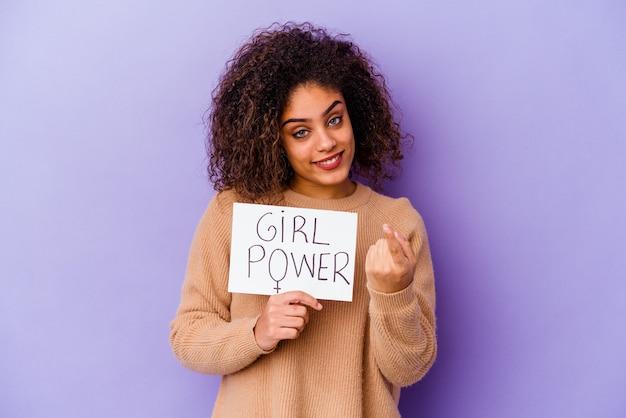 Junge afroamerikanerin, die ein girl-power-plakat hält, das auf violettem hintergrund isoliert ist und mit dem finger auf sie zeigt, als ob sie einladend näher kommen würde