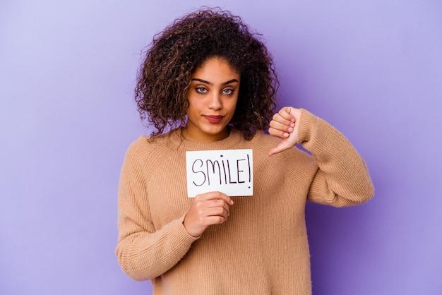 Junge afroamerikanerin, die ein lächeln-plakat hält, das auf violettem hintergrund isoliert ist und eine abneigungsgeste zeigt, daumen nach unten. meinungsverschiedenheit konzept.