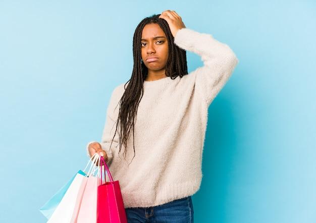 Junge afroamerikanerin, die eine einkaufstasche hält, die geschockt wird, sie hat wichtige erinnerung erinnert.