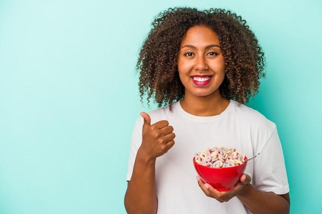 Junge afroamerikanerin, die eine schüssel müsli auf blauem hintergrund hält, lächelt und hebt den daumen