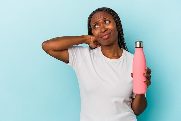 Junge afroamerikanerin, die kantine auf blauem hintergrund hält, die den hinterkopf berührt, nachdenkt und eine wahl trifft.