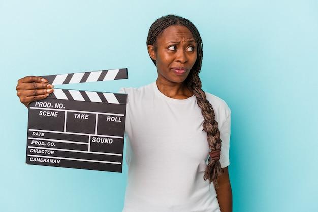 Junge afroamerikanerin, die klappe isoliert auf blauem hintergrund hält, verwirrt, fühlt sich zweifelhaft und unsicher.