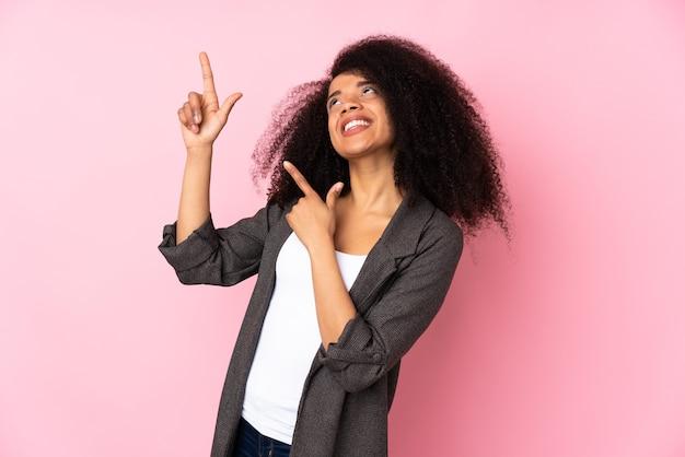 Junge afroamerikanerin, die mit dem zeigefinger eine große idee zeigt
