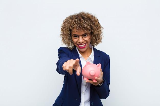Junge afroamerikanerin, die mit einem zufriedenen, selbstbewussten, freundlichen lächeln zeigt und sie mit einem sparschwein wählt