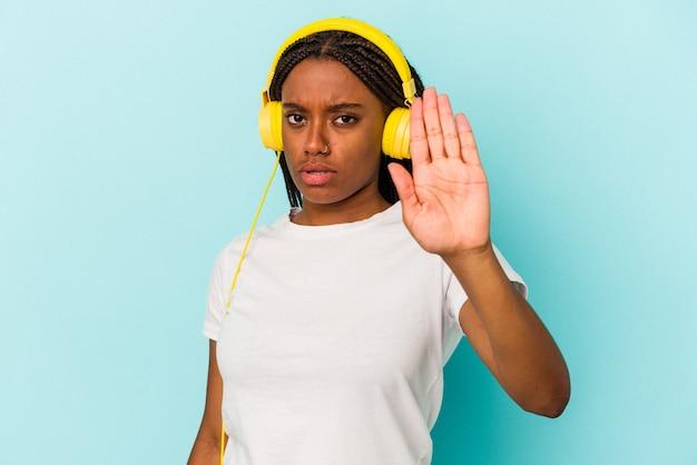 Junge afroamerikanerin, die musik hört, die auf blauem hintergrund lokalisiert wird, die mit ausgestreckter hand steht, die stoppschild zeigt und sie verhindert.