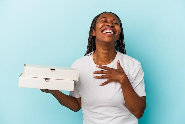 Junge afroamerikanerin, die pizzas einzeln auf blauem hintergrund hält, lacht laut und hält die hand auf der brust.