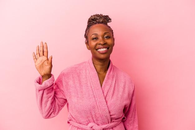Junge afroamerikanerin, die rosafarbenen bademantel trägt, isoliert auf rosafarbenem hintergrund, lächelt fröhlich und zeigt nummer fünf mit den fingern.