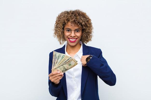 Junge afroamerikanerin, die sich glücklich, überrascht und stolz fühlt und mit einem aufgeregten, erstaunten blick mit euro-banknoten auf sich selbst zeigt