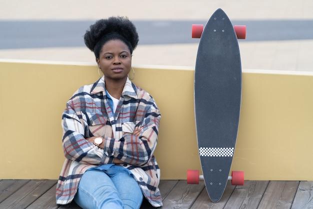 Junge afroamerikanerin, die sich nach dem skateboarden auf der stadtstraße in der nähe des flusses entspannt, sitzt ruhig neu. schwarze tausendjährige frau allein mit longboard-überlegung. urbanes lifestyle- und freizeitkonzept