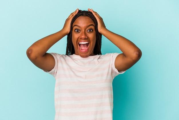 Junge afroamerikanerin einzeln auf blauem hintergrund schreiend, sehr aufgeregt, leidenschaftlich, zufrieden mit etwas.