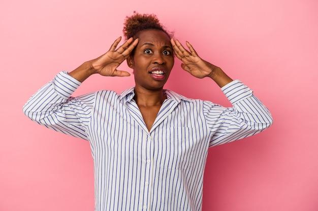 Junge afroamerikanerin einzeln auf rosafarbenem hintergrund, die eine angenehme überraschung empfängt, aufgeregt und die hände hebt.