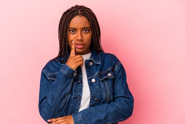 Junge afroamerikanerin einzeln auf rosafarbenem hintergrund, die seitlich mit zweifelhaftem und skeptischem ausdruck schaut.