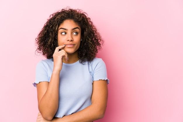 Junge afroamerikanerin gegen eine rosa wand junge afroamerikanerin gegen eine rosa wand entspanntes denken über etwas, das einen kopienraum betrachtet.