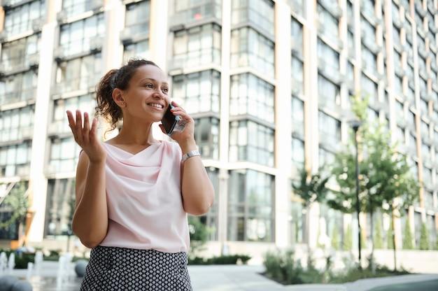 Junge afroamerikanerin gemischter rassen, die auf dem hintergrund der städtischen hochhäuser telefoniert. geschäfts- und kommunikationskonzepte