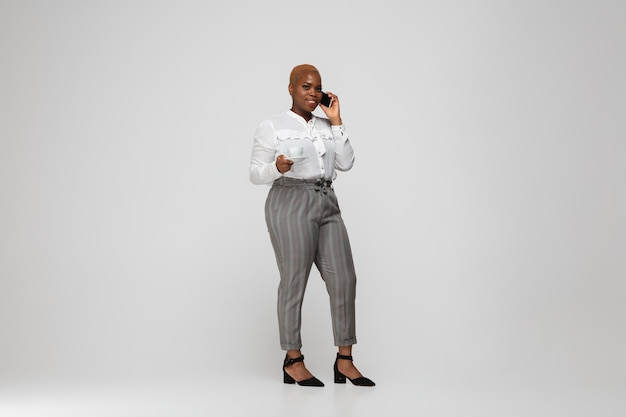 Junge afroamerikanerin in freizeitkleidung auf grau