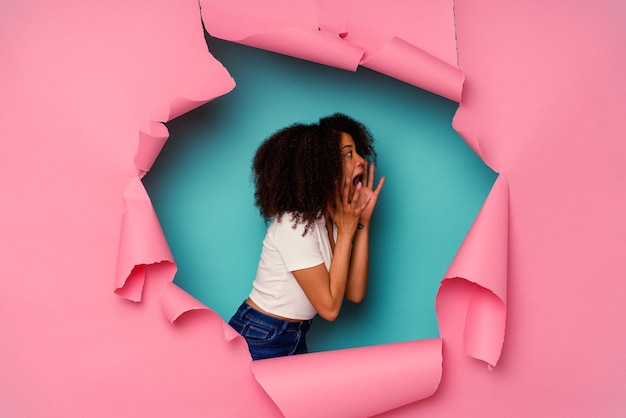 Junge afroamerikanerin in zerrissenem papier einzeln auf blau schreit laut, hält die augen geöffnet und die hände angespannt.