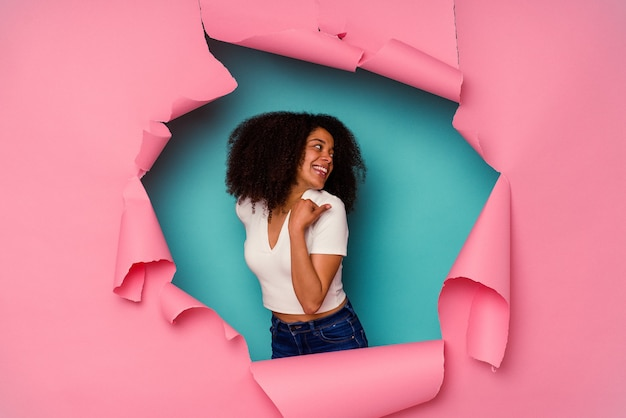 Junge afroamerikanerin in zerrissenem papier einzeln auf blauem hintergrund zeigt mit daumenfinger weg, lacht und sorglos.