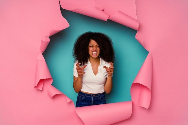 Junge afroamerikanerin in zerrissenem papier isoliert auf blauem umkippen, das mit angespannten händen schreit.
