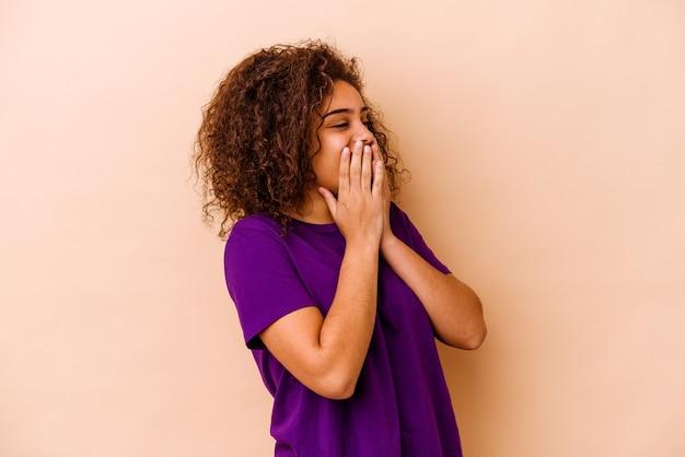 Junge afroamerikanerin isoliert auf beigem hintergrund, die über etwas lacht und den mund mit den händen bedeckt.