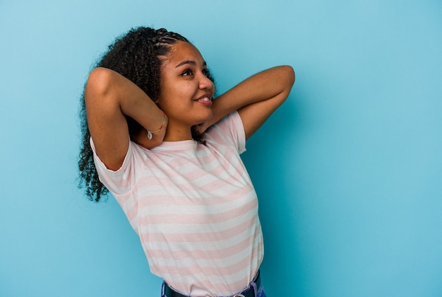 Junge afroamerikanerin isoliert auf blauem hintergrund, die sich selbstbewusst fühlt, mit den händen hinter dem kopf.