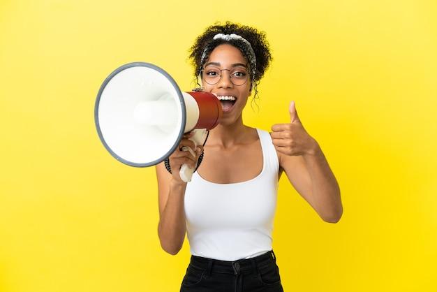Junge afroamerikanerin isoliert auf gelbem hintergrund, die durch ein megaphon schreit, um etwas anzukündigen und mit daumen nach oben