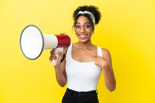 Junge afroamerikanerin isoliert auf gelbem hintergrund, die ein megaphon hält und mit überraschtem gesichtsausdruck