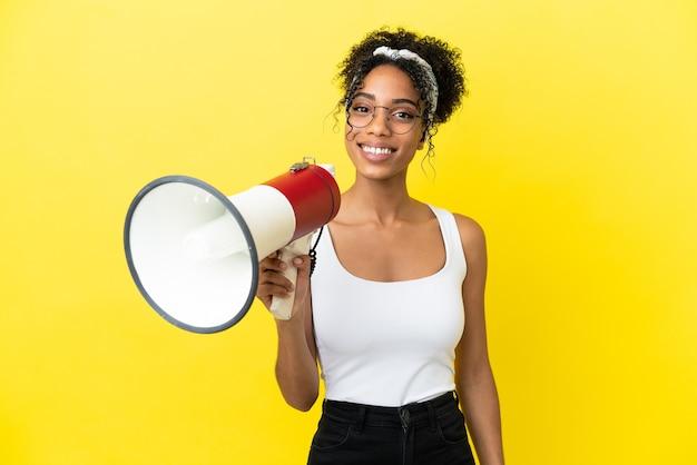 Junge afroamerikanerin isoliert auf gelbem hintergrund, die ein megaphon hält und viel lächelt