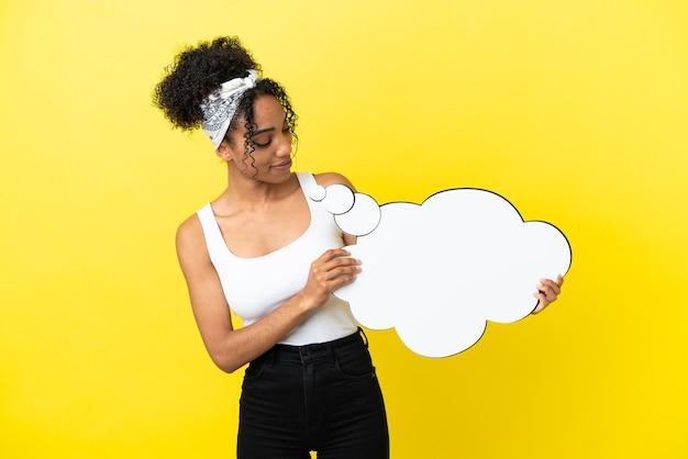 Junge afroamerikanerin isoliert auf gelbem hintergrund, die eine denkende sprechblase hält