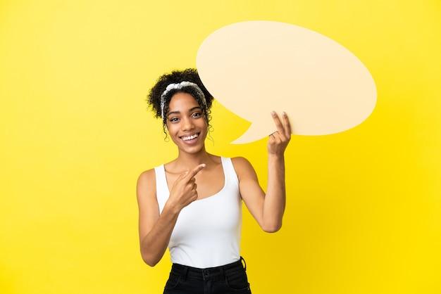 Junge afroamerikanerin isoliert auf gelbem hintergrund, die eine leere sprechblase hält und darauf zeigt