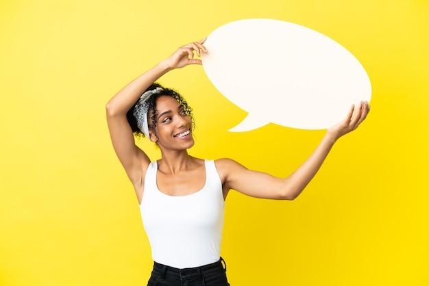 Junge afroamerikanerin isoliert auf gelbem hintergrund, die eine leere sprechblase hält