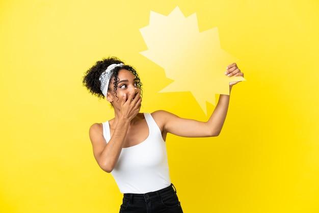 Junge afroamerikanerin isoliert auf gelbem hintergrund, die eine leere sprechblase mit überraschtem ausdruck hält