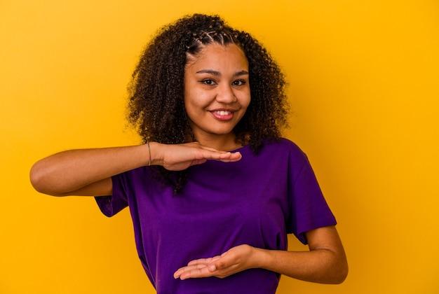 Junge afroamerikanerin isoliert auf gelbem hintergrund, die etwas mit beiden händen hält, produktpräsentation.