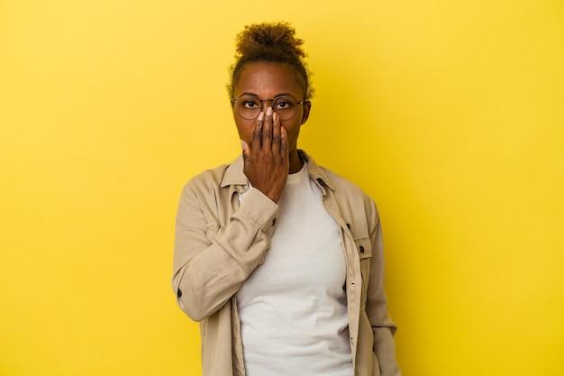 Junge afroamerikanerin isoliert auf gelbem hintergrund schockiert, bedeckt den mund mit den händen, begierig, etwas neues zu entdecken.