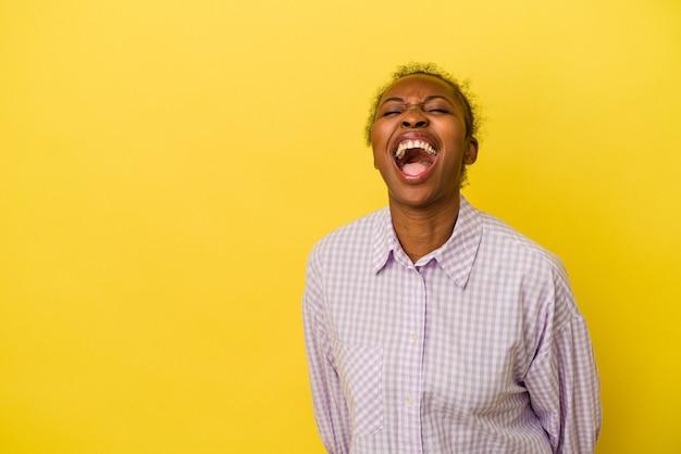 Junge afroamerikanerin isoliert auf gelbem hintergrund schreien sehr wütend, wutkonzept, frustriert.
