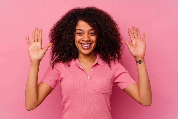 Junge afroamerikanerin isoliert auf rosa, die eine angenehme überraschung empfängt, aufgeregt und die hände hebt.