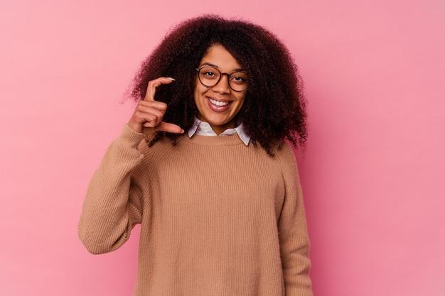 Junge afroamerikanerin isoliert auf rosa, die etwas kleines mit den zeigefingern hält, lächelnd und selbstbewusst.