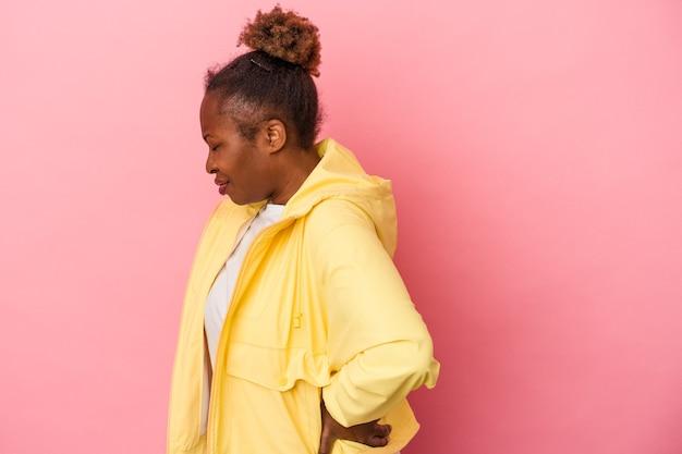 Junge afroamerikanerin isoliert auf rosa hintergrund, die an rückenschmerzen leidet.