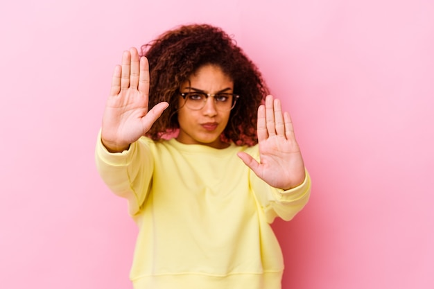 Junge afroamerikanerin isoliert auf rosafarbenem hintergrund, die mit ausgestreckter hand steht und stoppschild zeigt und sie verhindert.