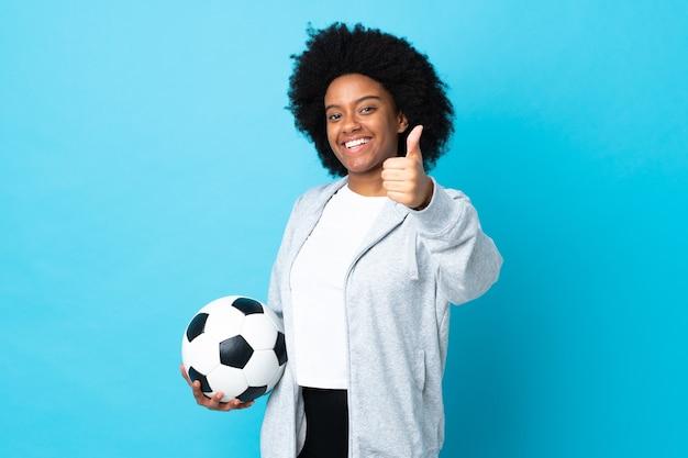 Junge afroamerikanerin lokalisiert auf blau mit fußball und mit daumen nach oben