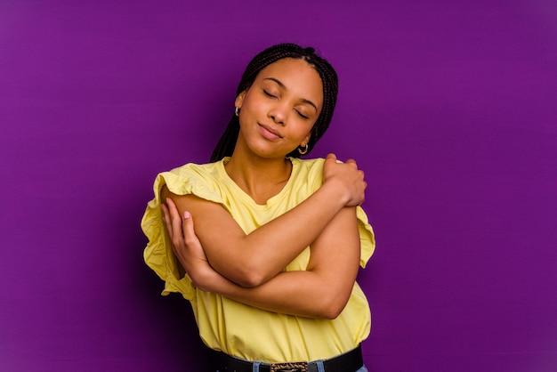 Junge afroamerikanerin lokalisiert auf gelbem hintergrund junge afroamerikanerin isoliert auf gelbem hintergrund umarmt, lächelt sorglos und glücklich.