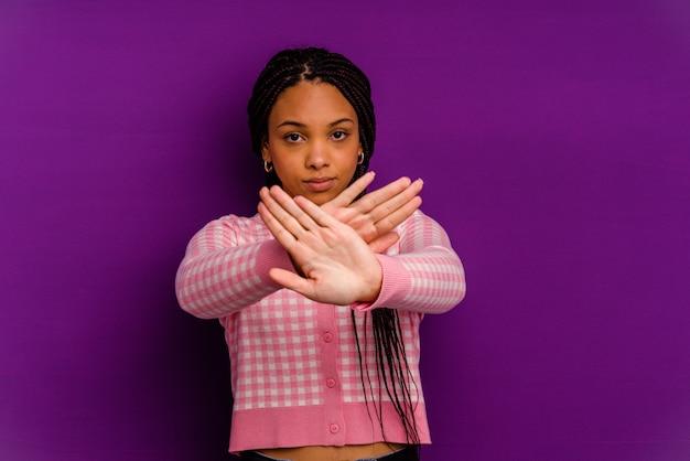 Junge afroamerikanerin lokalisiert auf gelber wand junge afroamerikanerin isoliert auf gelber wand, die eine verweigerungsgeste tut