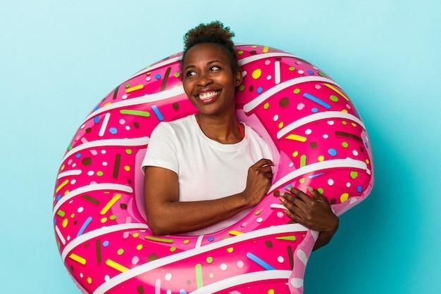 Junge afroamerikanerin mit aufblasbarem donut einzeln auf blauem hintergrund sieht beiseite lächelnd, fröhlich und angenehm aus.