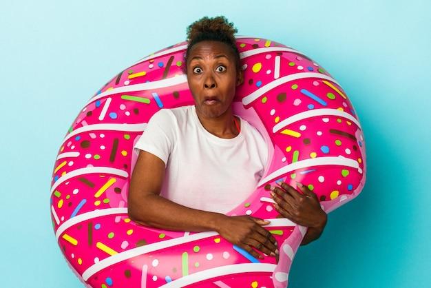 Junge afroamerikanerin mit aufblasbarem donut einzeln auf blauem hintergrund zuckt mit den schultern und offenen augen verwirrt.