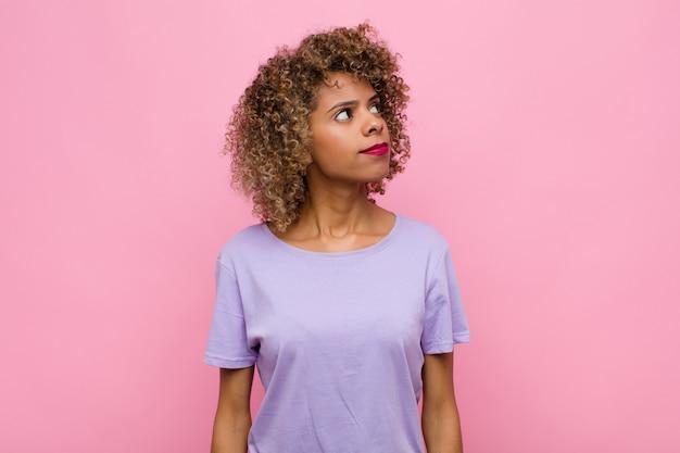 Junge afroamerikanerin mit einem besorgten, verwirrten, ahnungslosen ausdruck, der aufschaut, um raum zu kopieren, zweifel an rosa wand
