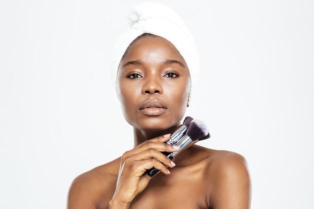 Junge afroamerikanerin mit handtuch auf dem kopf, die make-up-pinsel auf weißem hintergrund hält