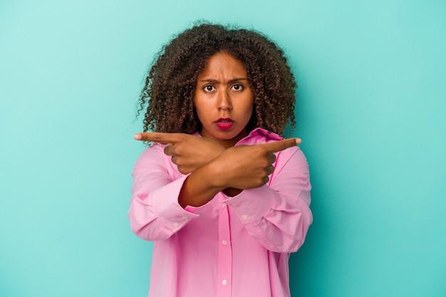 Junge afroamerikanerin mit lockigem haar, die auf blauem hintergrund isoliert ist, zeigt seitlich, versucht, zwischen zwei optionen zu wählen.